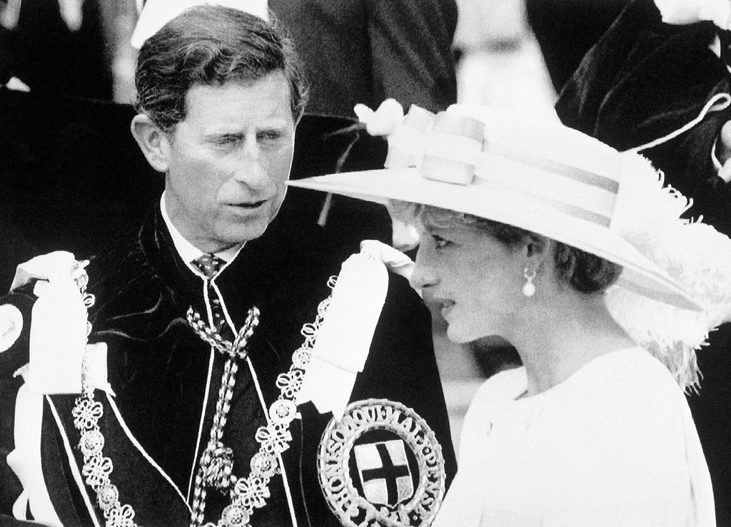 . Britain\'s Prince of Wales, wearing the robes of the Order of the Garter, looks towards the Princess of Wales, Princess Diana, as they await a carriage to depart the Order of the Garter Service at Windsor Castle, England on June 15, 1992.  (AP Photo/Pool)