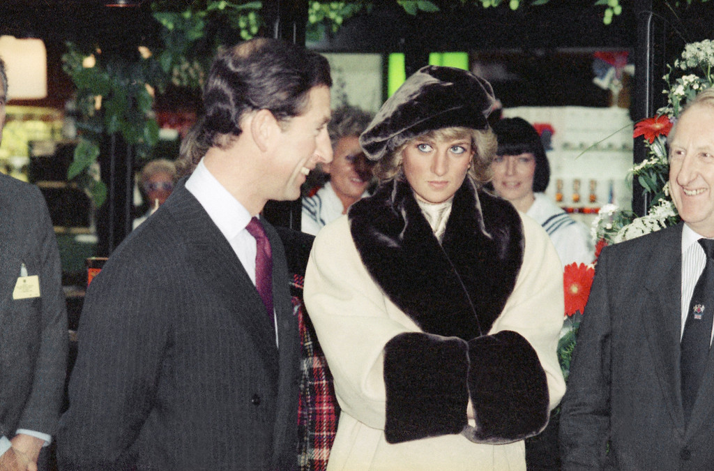. Princess Diana uses the coat sleeves as a muff as she warms her hands while looking to her husband Prince Charles as the royal couple visits a department store in Hamburg, West Germany, Nov. 6, 1987. Princess Diana wears a crème woolen coat with imitation fur trimming with matching hat. (AP Photo/Heribert Proepper)