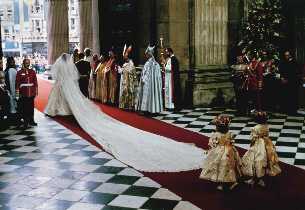 . With a 25-foot (7.6 meter) sweeping train, The Princess of Wales, former Lady Diana Spencer, leaves St. Paul\'s Cathedral arm in arm with Prince Charles at the end of their wedding ceremony in London, July 29, 1981. (AP Photo)