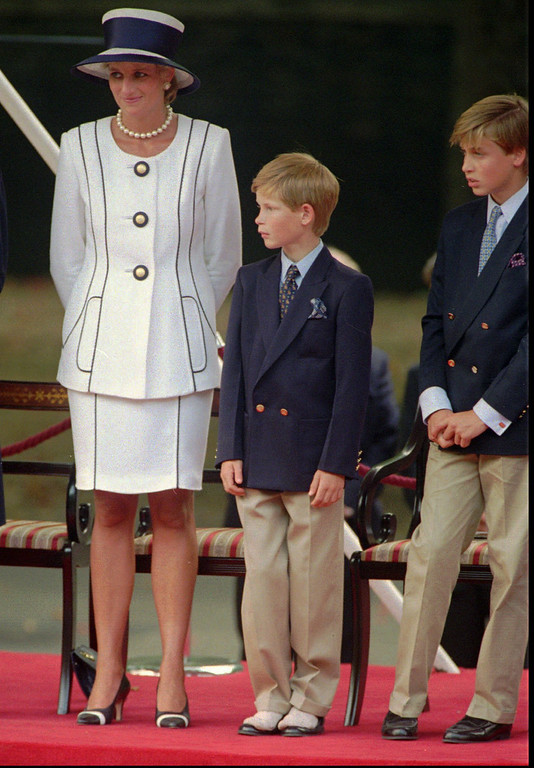 . Britain\'s Prince Harry, center, 10 year old son of Princess Diana and Prince Charles, stands on top of his shoes next to his mother and brother Prince William, as they watch the V-J Day veterans parade in Central London, Saturday August 19, 1995.  (AP Photo/Alastair Grant, Pool)