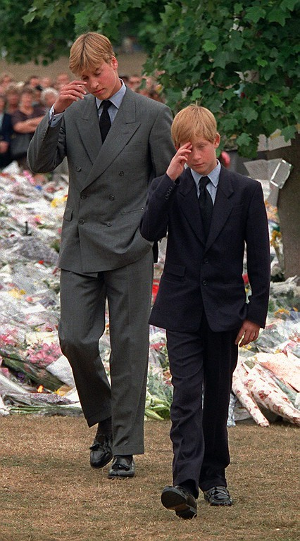 . Prince William, left, and Prince Harry gesture after they arrived at  Kensington Palace to view some of the flowers and mementos left in memory of their mother Princess Diana in London, Friday, Sept. 5, 1997.  (AP Photo/David Brauchli)