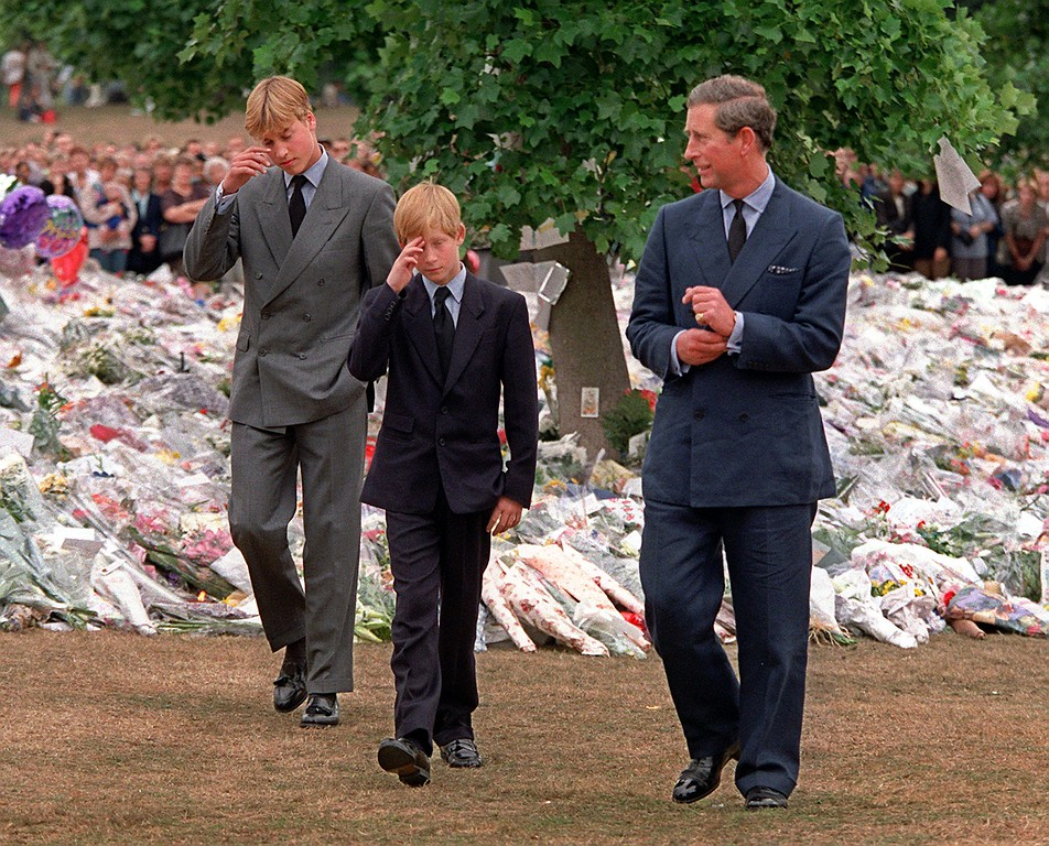 . Prince Charles, right, accompanies his sons Prince William, left and Prince Harry after they arrived at Kensington Palace to view tributes left in memory of their mother Princess Diana in London, Friday, Sept. 5, 1997.  (AP Photo/David Brauchli)