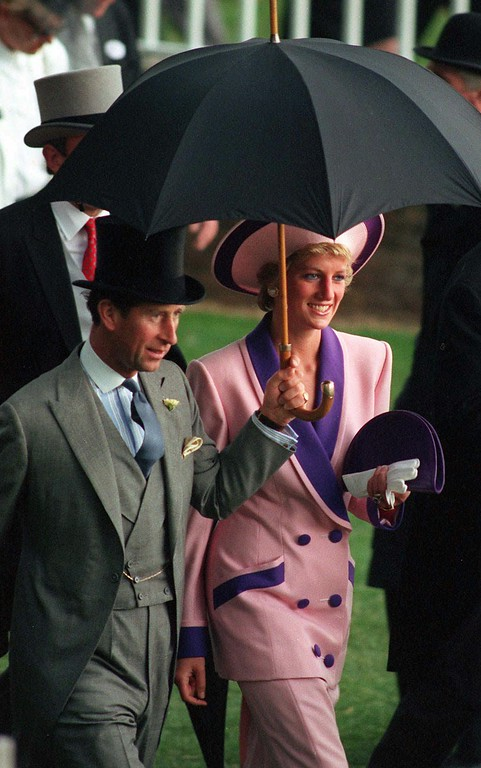 . The Prince and Princess of Wales take shelter under an umbrella while attending the second day of the Royal Ascot horse race meet near London, Wednesday, June 20, 1990. (AP Photo/Martyn Hayhow)