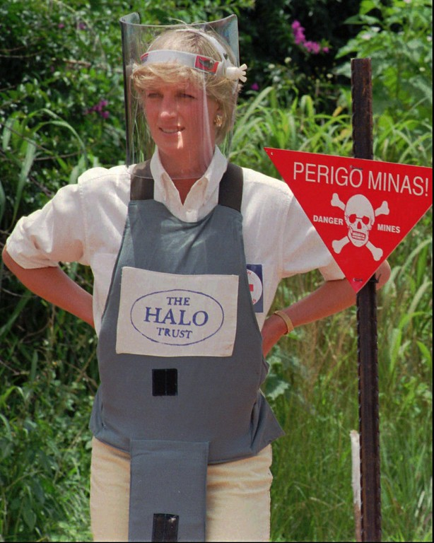 """. Diana, Princess of Wales, wearing protective gear, in this Wednesday , 1997 file photo, during a briefing by the British land-mine sweeping organisation Halo Trust in Huambo, cenrtal Angola, one of the most densely mined areas in the country. The sign reads \""""Danger-Mines\"""". Diana was visiting Angola in an effort to raise awareness on the problems of landmines. (AP Photo/Giovanni Diffidenti)"""
