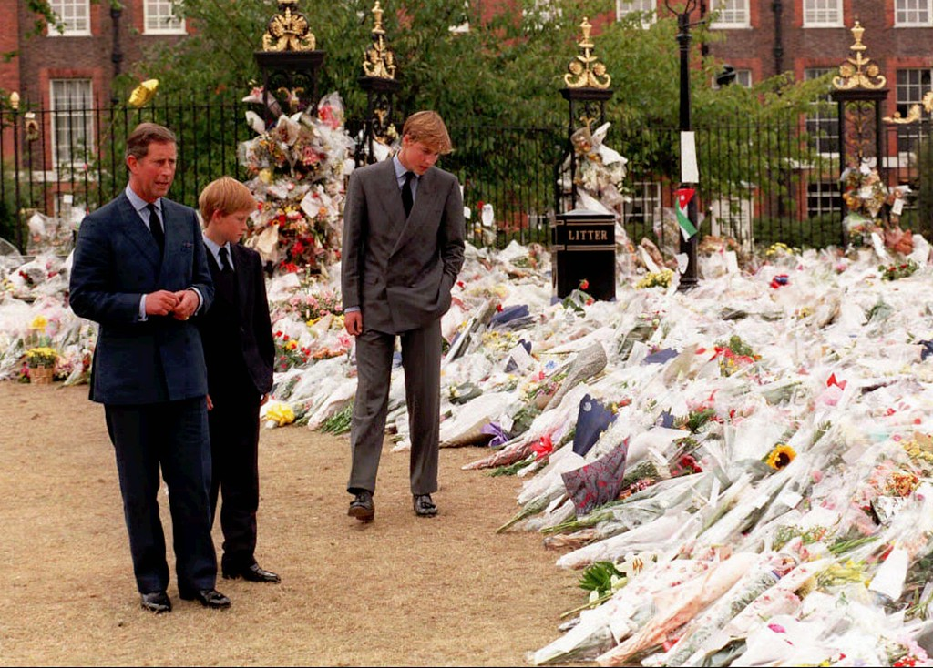 . The Prince of Wales, left, and his sons Prince William, third from left, and Prince Harry, second from left, view the sea of floral tributes to their mother, Diana, Princess of Wales, at Kensington Palace, in background, Friday Sept. 5 1997.  (AP Photos/Rebecca Naden/POOL)
