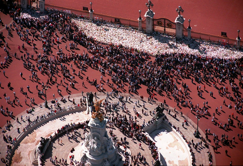 . This is an aerial view showing a large pile of flowers and other momentos to the late Princess Diana at the gates of Buckingham Palace in London, as the crowds continue to arrive to pay their respects Thursday, Sept. 4, 1997. Seen at the bottom center of this frame is the Queen Victoria Memorial.  (AP Photo/Adrian Dennis)