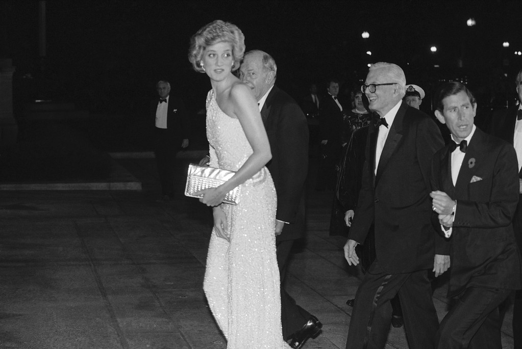 . Princess Diana, smiles to reporters as she arrives at the National Gallery of Art for dinner in Washington on Nov. 10, 1986. The princess is escorted into the museum by John Stevenson, president of the gallery. (AP Photo/Ira Schwarz)