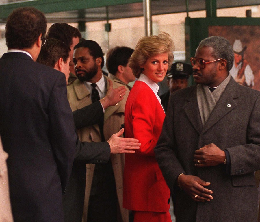 . Princess Diana, wearing a fire engine red suit, is surrounded by security people on Feb. 3, 1989, as she is escorted into Harlem Hospital in New York City. The Princess of Wales then toured an AIDS pediatric ward. (AP photo//Richard Drew)