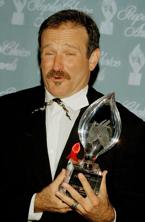 ". Robin Williams mugs as he cradles the People\'s Choice award he won for Best Actor in a Comedy Motion Picture at the 20th Annual People\'s Choice Awards at Sony Pictures Studios in Culver City, Calif., March 8, 1994. Williams won the award for his role in ""Mrs. Doubtfire,\"" which also won the Best Comedy Motion Picture. (AP Photo/Reed Saxon)"