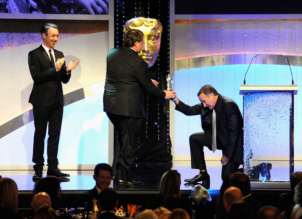 . Actor Robin Williams presents honoree John Lasseter with the Albert R. Broccoli Britannia Award for Worldwide Film Contribution onstage at BAFTA Los Angeles 2011 Britannia Awards at The Beverly Hilton hotel on November 30, 2011 in Beverly Hills, California.  (Photo by Frazer Harrison/Getty Images For BAFTA Los Angeles)