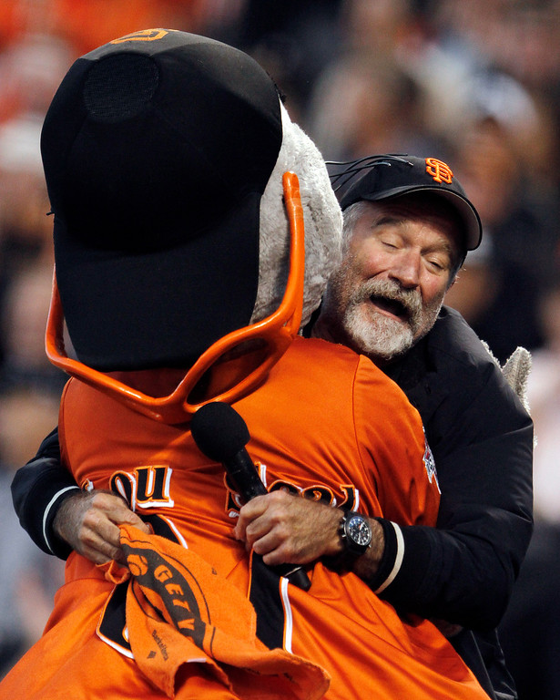 . FILE - In this file photo from Thursday, Oct. 7, 2010, actor Robin Williams hugs San Francisco Giants mascot Lou Seal during the first inning of Game 1 of baseball\'s National League Division Series in San Francisco.  (AP Photo/Ben Margot, File)