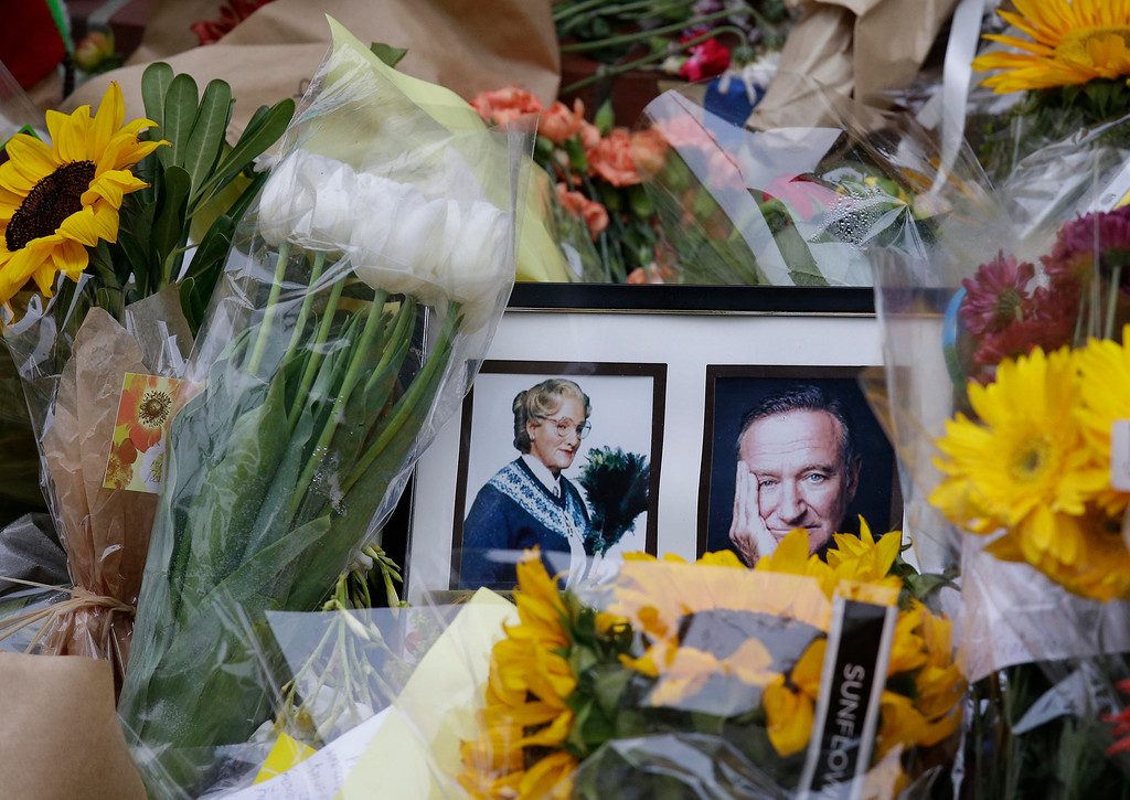 ". Flowers and photographs are displayed Friday, Aug. 15, 2014, in San Francisco, of a makeshift memorial for actor Robin Williams outside a home which was used in the filming of the movie ""Mrs. Doubtfire.\""  (AP Photo/Eric Risberg)"