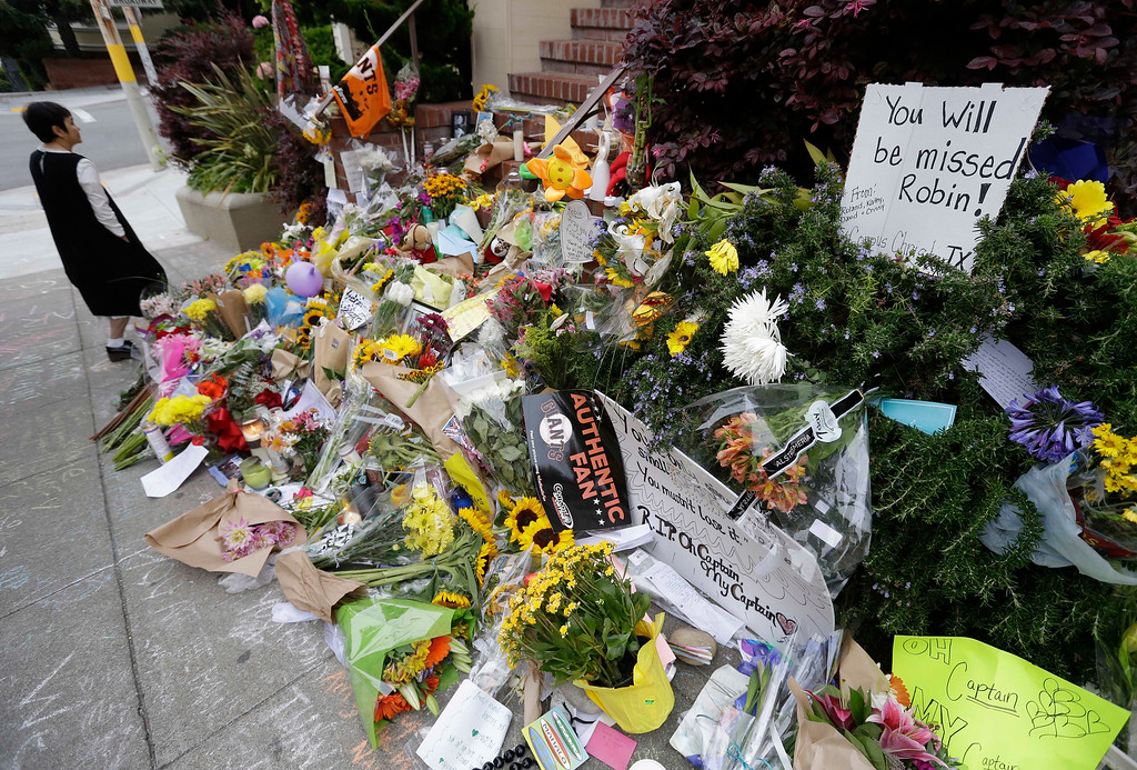 ". A woman stops to look at a makeshift memorial,  Friday, Aug. 15, 2014, in San Francisco, for actor Robin Williams outside a home which was used in the filming of the movie ""Mrs. Doubtfire.\""  (AP Photo/Eric Risberg)"