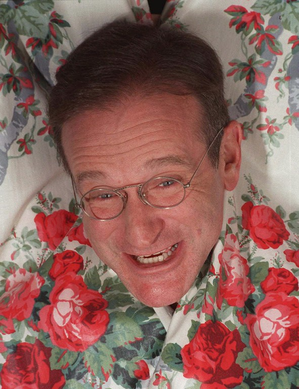 """. In this Nov. 15, 1997 file photo, Robin Williams extends his head between curtains in a New York hotel. Williams, a brilliant shapeshifter who could channel his frenetic energy into delightful comic characters like \""""Mrs. Doubtfire\"""" or harness it into richly nuanced work like his Oscar-winning turn in \""""Good Will Hunting,\"""" died Monday, August 11, 2014.  (AP Photo/Jim Cooper, File)"""