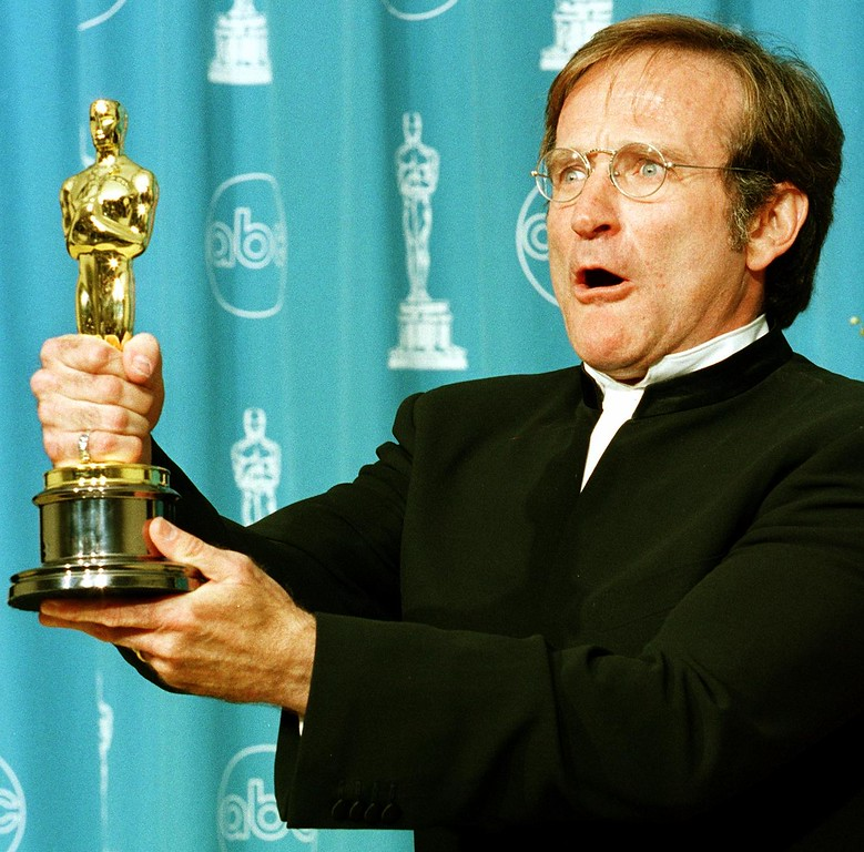 """. File - Actor Robin Williams holds the Oscar he won for Best Supporting Actor for his role in \""""Good Will Hunting\"""" during the 70th Annual Academy Awards 23 March in Los Angeles, CA. Williams was born on July 21, 1951, in Chicago, Illinois. He died August 11, 2014 at the age of 63. (HAL GARB/AFP/Getty Images)"""