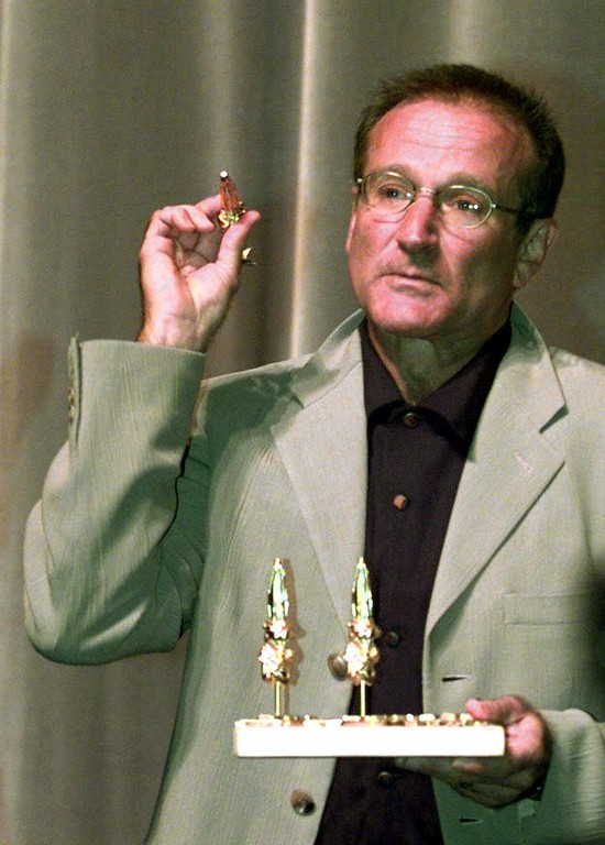 . American movie star Robin Williams plays with a piece of the trophy he received for his career at the Film Festival in Deauville, Normandy, Tuesday, Sept. 7, 1999.   (AP Photo/Franck Prevel)