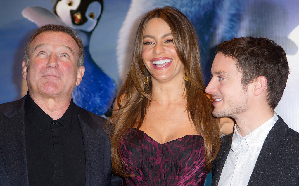 . Actors, from left, Robin Williams, Sophia Vergara and Elijah Wood react as they arrive for the European premiere of Happy Feet Two at a central London cinema, Sunday, Nov. 20, 2011. (AP Photo/Joel Ryan)