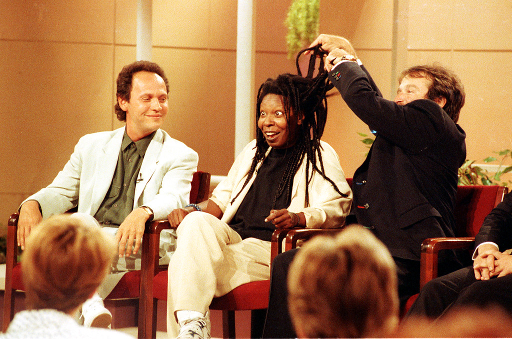 ". Whoopi Goldberg reacts as Robin Williams lifts her hair while appearing on the ""Donahue Show\"" with Billy Crystal, left, in New York City, May 9, 1990.  (AP Photo/Marty Lederhandler)"