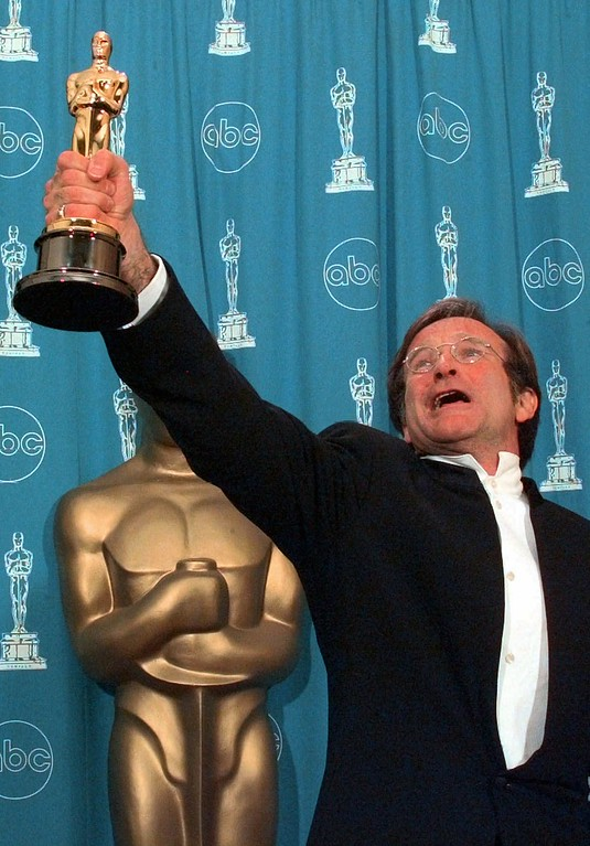 ". Robin Williams holds his Oscar high backstage at the 70th Academy Awards at the Shrine Auditorium in Los Angeles Monday, March 23, 1998. Williams won Best Supporting Actor for ""Good Will Hunting.\"" (AP Photo/Reed Saxon)"