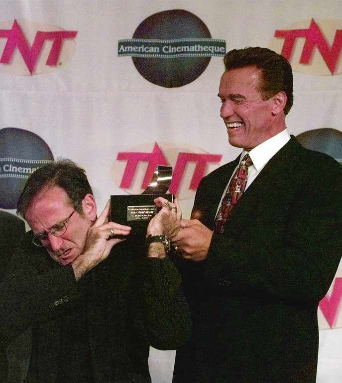 . Actor Robin Williams, left, passes the 1998 American Cinematheque Award to fellow actor Arnold Schwarzenegger during the 13th annual Moving Picture Ball in Beverly Hills, Calif.,  Sunday, Oct. 18, 1998.  (AP Photo/Michael Caulfield)