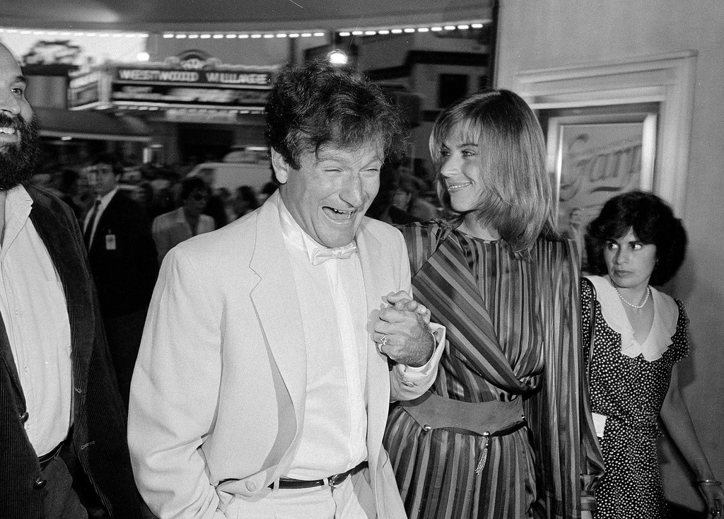 """. Robin Williams breaks into laughter as he and his wife, Valerie Velardi, hurry into Mann\'s Bruin Theater for the world benefit premiere of the new film \""""The World According to Garp,\"""" in Los Angeles, Calif., July 14, 1982. . (AP Photo/Reed Saxon)"""