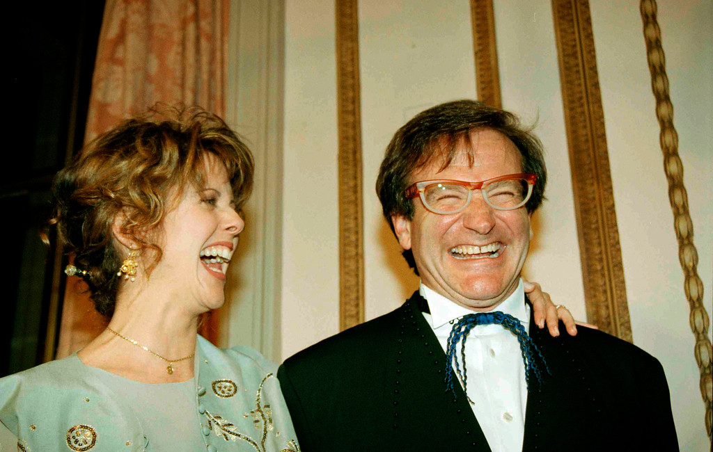 """. Robin Williams, right, shares a laugh with Pam Dawber, his former co-star on old TV sitcom \""""Mork & Mindy\"""" upon her arrival at the Waldorf-Astoria Hotel in New York, Feb. 23, 1995.  (AP Photo/Eric Miller)"""
