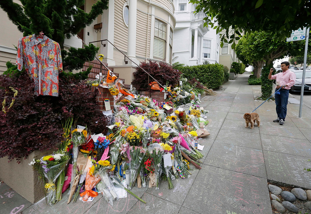 ". A man stops with his dog to take a picture Friday, Aug. 15, 2014, in San Francisco, of a makeshift memorial for actor Robin Williams outside a home which was used in the filming of the movie ""Mrs. Doubtfire.\""  (AP Photo/Eric Risberg)"