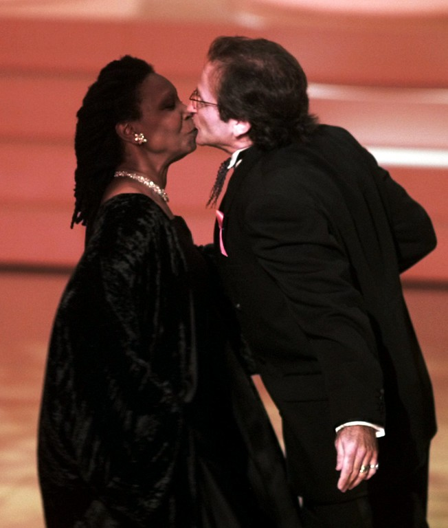 . Host Whoopi Goldberg kisses Robin Williams who presented an award at the 68th Annual Academy Awards in Los Angeles, Monday, March 25, 1996. (AP Photo/Eric Draper)