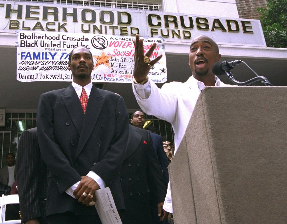 ". File - Rapper Tupac Shakur, right, speaks as fellow rap artist Snoop Doggy Dogg listens during a voter registration rally in South Central Los Angeles on August 15, 1996.  Late Saturday night, September 7, 1996, Shakur and Death Row Records chairman Marion ""Suge\"" Knight were shot in their car as they drove through the Las Vegas Strip area.  (AP Photo/Frank Wiese)"