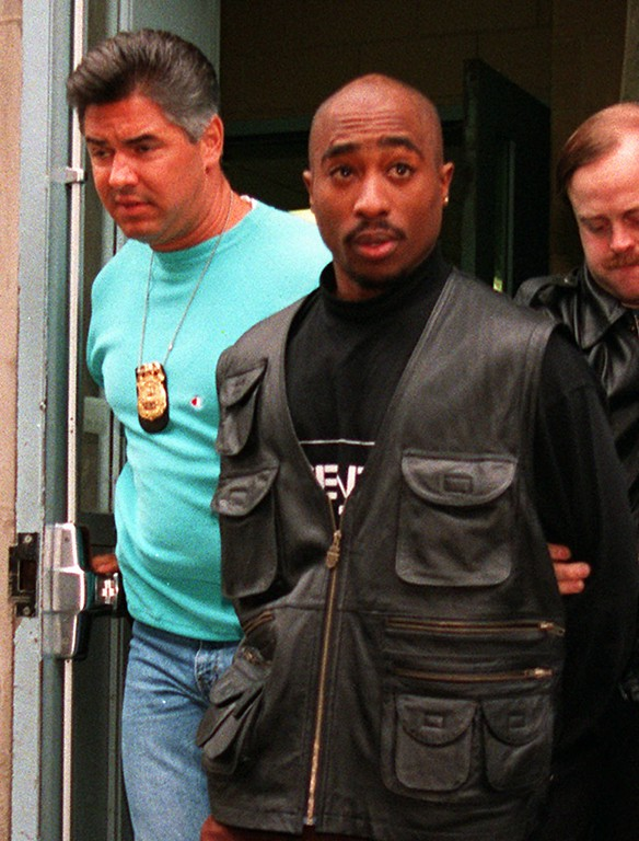 . Rap star Tupac Shakur is led from the Manhattan North police precinct after being arrested in an alleged sexual attack on Nov. 19, 1993.  (AP Photo/Justin Sutcliffe)