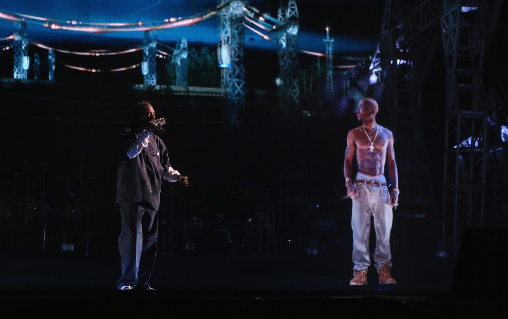 . Rapper Snoop Dogg (L) and a hologram of deceased rapper Tupac Shakur perform onstage during day 3 of the 2012 Coachella Valley Music & Arts Festival at the Empire Polo Field on April 15, 2012 in Indio, California.  Shakur died on September 13, 1996. (Photo by Christopher Polk/Getty Images for Coachella)