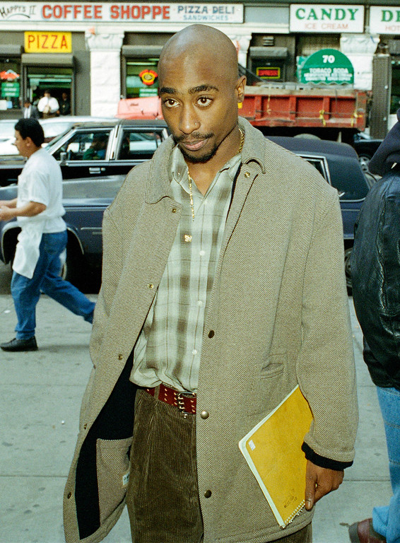 . Rapper Tupac Shakur holds a notebook as he waits in line to pass through the metal detectors at New York State Supreme Court in Manhattan, Nov. 14, 1994.  (AP Photo/Robert Kalfus)