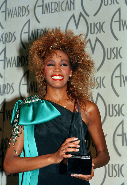 . Singer Whitney Houston shows her American Music Award, at the Shrine Auditorium in Los Angeles, Calif., Jan. 27, 1986.  (AP Photo)