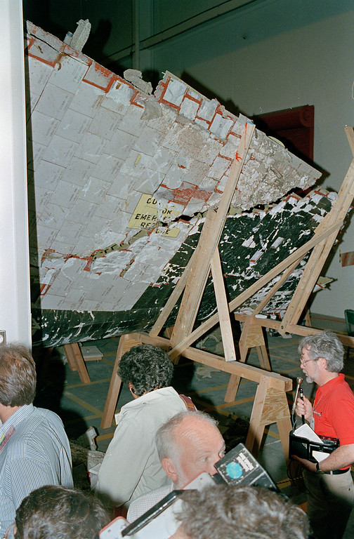 . Reporters and photographers examine the wreckage of the space shuttle Challenger for the first time, April 9, 1986, at the Kennedy Space Center.  The Challenger exploded just after lift off on Jan. 28, killing all seven crew members aboard.  (AP Photo/Pool)