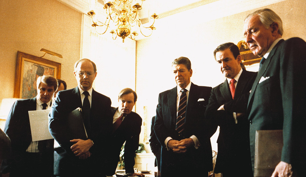 . U.S. President Ronald Reagan, center, is surrounded by members of his senior staff as he watches a TV replay of the explosion of the Challenger space shuttle, on February 3, 1986, at the White House in Washington. From left are: Larry Speakes, deputy White House press secretary; Presidential Assistant Dennis Thomas; Special Assistant Jim Kuhn; Reagan; White House Communications Director Patrick Buchanan, and Chief of Staff Donald Regan.  (AP Photo/Craig Fujii)