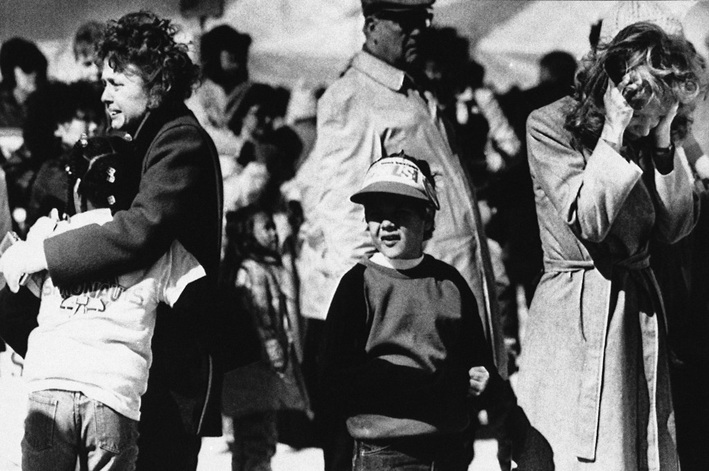 . Young Scott McAuliffe\'s third grade teacher comforts one of her charges as another youngster and a young woman, right, react after seeing the Space Shuttle Challenger explode in midair, killing all aboard, Tuesday, Jan. 28, 1986. The teacher and student are from the Kimbell Elementary School in Concord, N.H., where young McAuliffe, son of space school teacher Christa McAuliffe, is a student. (AP Photo)