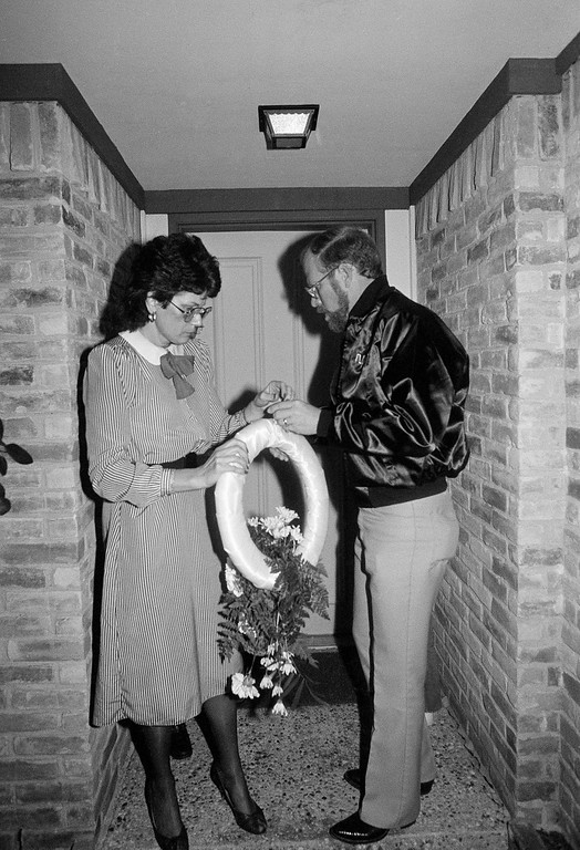 . Suzanne and Chris Butler prepare to put a wreath on the door of mission specialist Ellison Onizuka in Houston, Texas, Tuesday, Jan. 28, 1986. Onizuka was aboard the Space Shuttle Challenger when it exploded. (AP Photo)