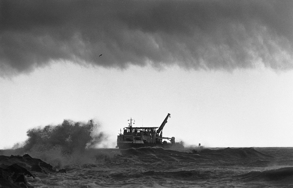 . The giant salvage ship, the Stener Workhorse comes to port as storm clouds darken overhead and waves crash against the jetties at Port Canaveral, Florida on Friday, March 14, 1986. The Stener Workhorse was one of the largest ships being used for salvage work in an area where Space Shuttle Challenger crashed into the sea following the explosion that ripped it apart on January 28th. (AP Photo/Thom Baur)