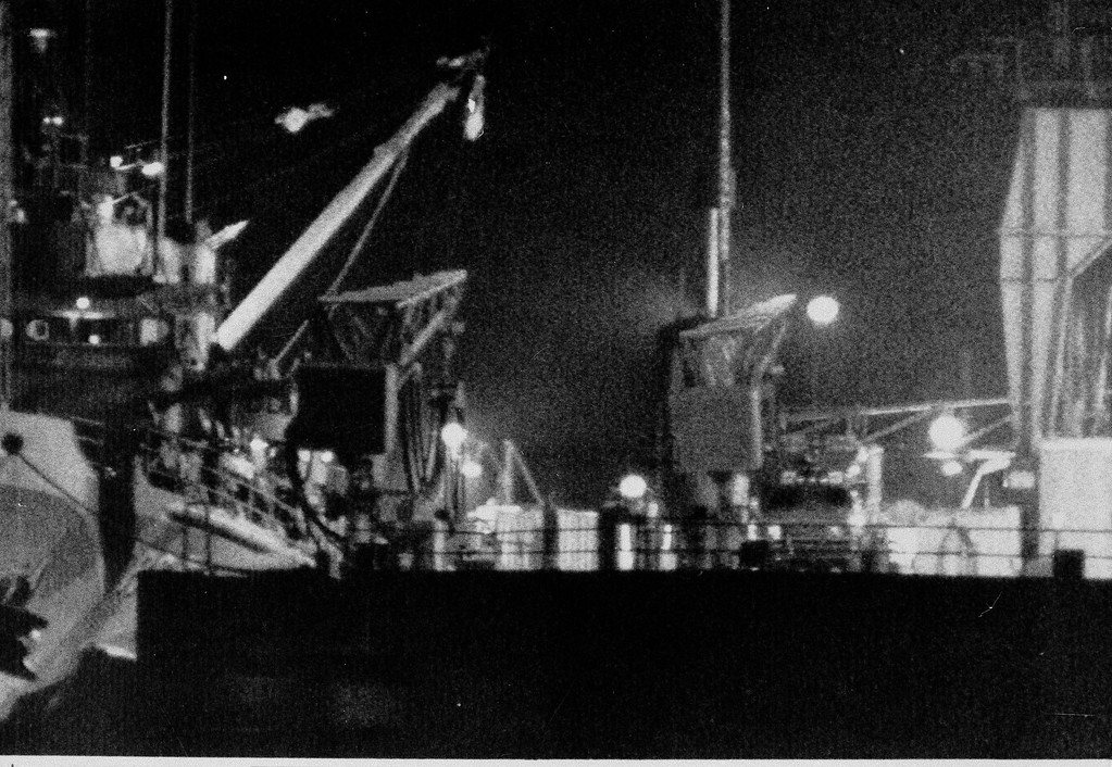 . A military ambulance, right of center with lights on, waits for the U.S.S. Preserver to unload its cargo after it arrived at the Trident Submarine Docks at Port Canaveral, March 17, 1986.  The Preserver was carrying debris from the space shuttle Challenger and reportedly the remains of crew members.  (AP Photo/Bruce Weaver)