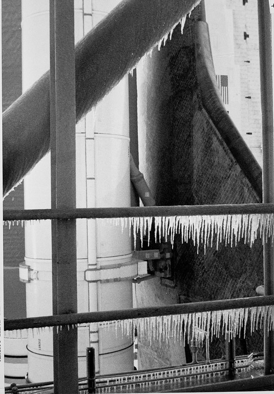 . Icicles are visible in this photo taken by a NASA ice inspection team the morning of the Space Shuttle Challenger\'s final launch, Kennedy Space Center, Fla., Jan. 28, 1986. The icicles are on hand rails and support structure of the Fixed Service Structure, which is used to service the shuttle just before launch. The shuttle, its external fuel tank, and left side solid rocket booster motor, are visible in the background. (AP Photo/NASA)