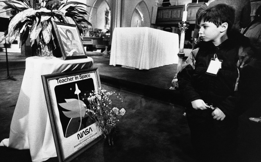 . An unidentified boy looks at a shrine set up in memory of Christa McAuliffe at St. John\'s Church in Concord, New Hampshire on Wednesday, Jan. 30, 1986, following a memorial service in her honor. McAuliffe was killed in the explosion of the Space Shuttle Challenger on Tuesday. (AP Photo/David Tenenbaum)