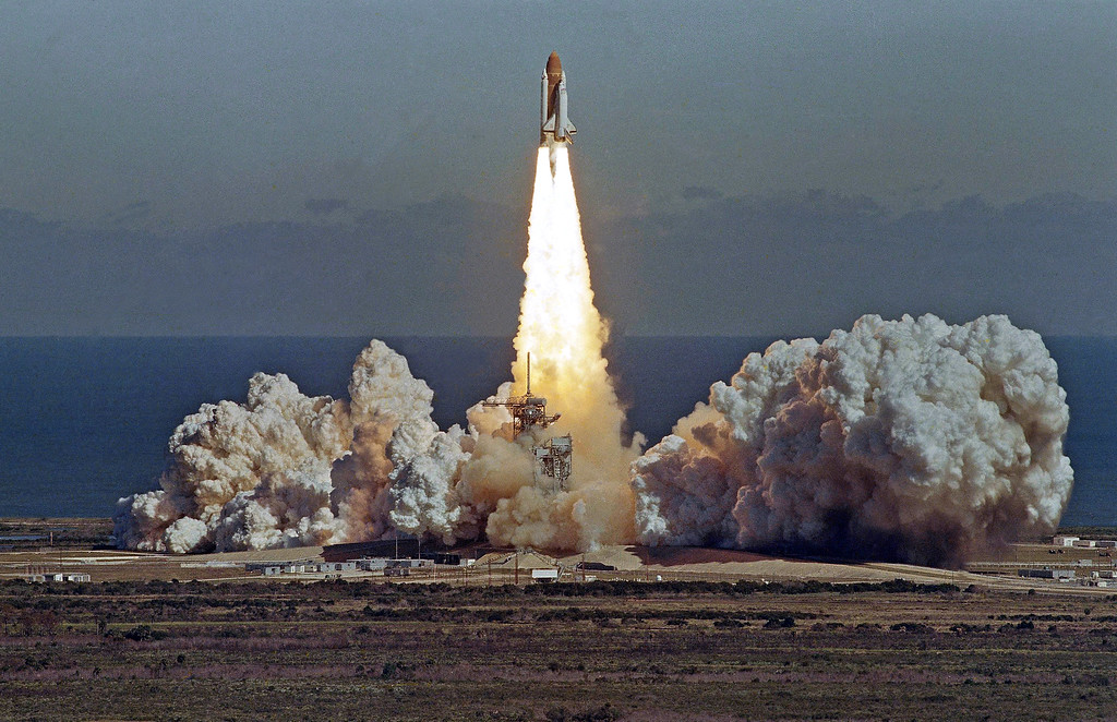 . The Space Shuttle orbiter Challenger lifts off from Kennedy Space Center, Florida, Jan. 28, 1986, in a cloud of smoke with a crew of seven aboard. The shuttle exploded after this photo, taken from atop the Vehicular Assembly Building, was made. (AP Photo/Thom Baur)