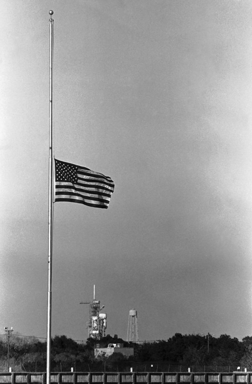 . The American flag in the press site at the Kennedy Space Center, Fla., flies at half-mast, Tuesday, Jan. 28, 1986, following the explosion of the Space Shuttle Challenger. NASA said the crew of seven aboard the craft died in the explosion. Launch pad B is shown under the flag. (AP Photo/Jim Cole)
