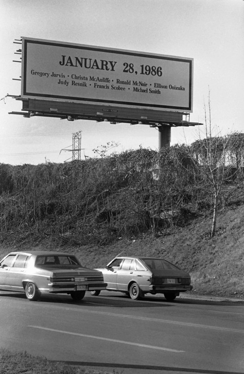 . A billboard showing the date of the space shuttle Challenger disaster along with the names of the seven astronauts who lost their lives aboard the shuttle stands on a hill overlooking motorists passing by on Pulaski Highway in Baltimore, Maryland on Jan. 31, 1986. (AP Photo/Joe Giza)