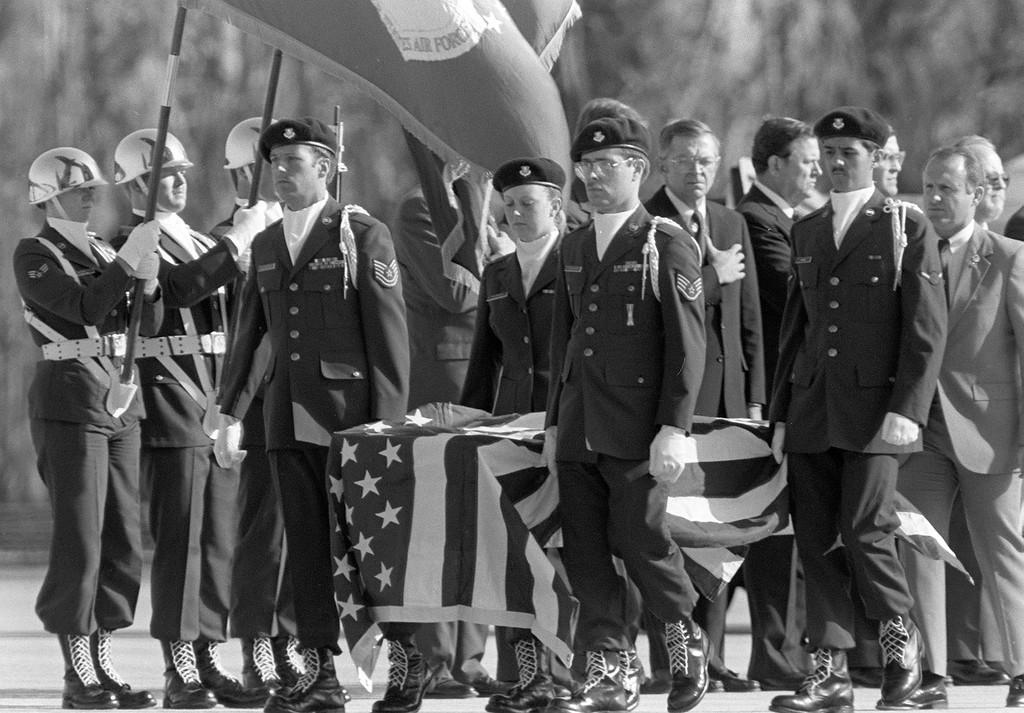 . A military honor guard carries the remains of one of the crew members of the Space Shuttle Challenger at Kennedy Space Center, Fla., on Tuesday, April 29, 1986, as the body was being transferred to Dover, Del. Seven crew members were killed in the Jan. 28th explosion. (AP Photo/Phil Sandlin)