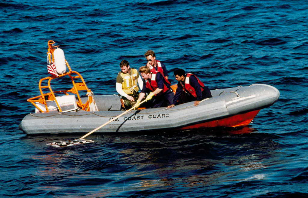 . Coast guardsmen retrieve debris from the space shuttle Challenger, Jan. 31, 1986, off the coast of Florida.  The Challenger exploded shortly after take off, killing its crew of seven.  (AP Photo/Pool)