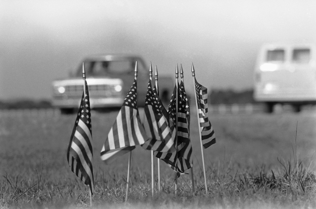 . Kennedy Space Center workers enroute to Pad 39B were met by the sight of seven small American flags along side the road, Jan. 30, 1986. Seven crew members were killed in the explosion of the Space Shuttle Challenger on Tuesday which was launched from Pad 39B. (AP Photo/Phil Sandlin)