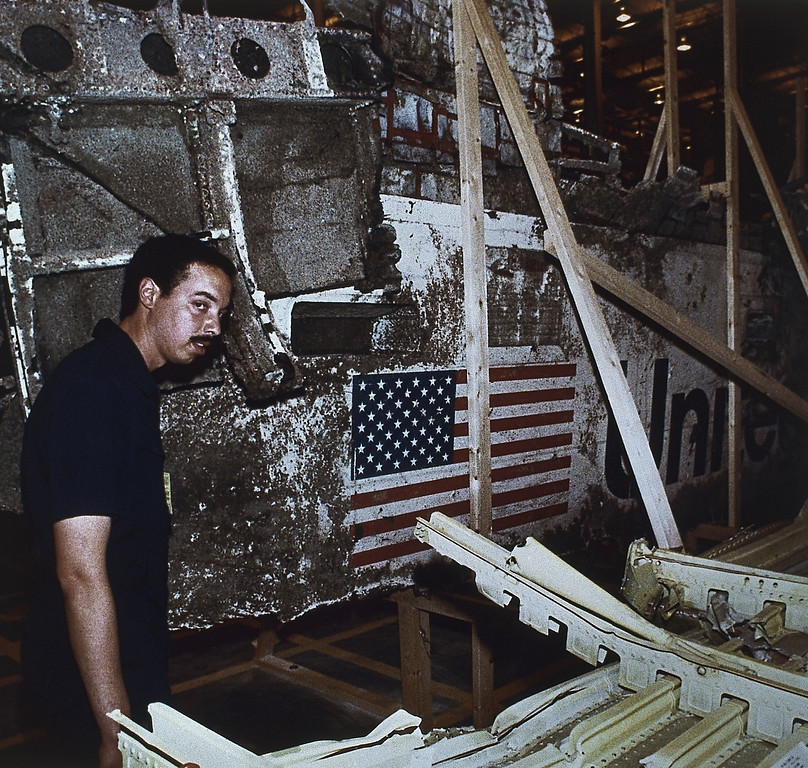 . John White, National Transportation Safety Board inspector, stands near the left side of the wreckage of the Space Shuttle Challenger, Wednesday, April 10, 1986, Kennedy Space Center, Fla. The press was allowed to view the Challenger wreckage for the first time. (AP Photo)