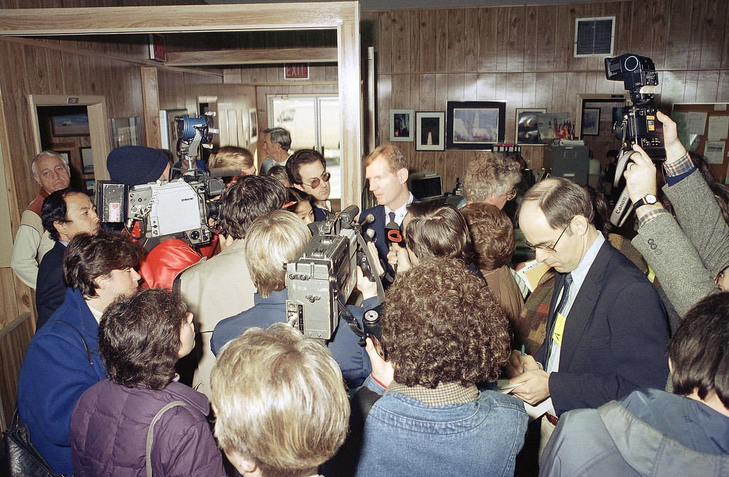 . Space Shuttle Challenger Flight 51-L, Lt. Commander Jim Simpson, briefs newsmen, Jan. 29, 1986, on the operation of Coast Guard ships searching the Atlantic Ocean off of the Kennedy Space Center, Florida for debris from the Space Shuttle Challenger which exploded after liftoff yesterday. (AP Photo/Thom Baur)