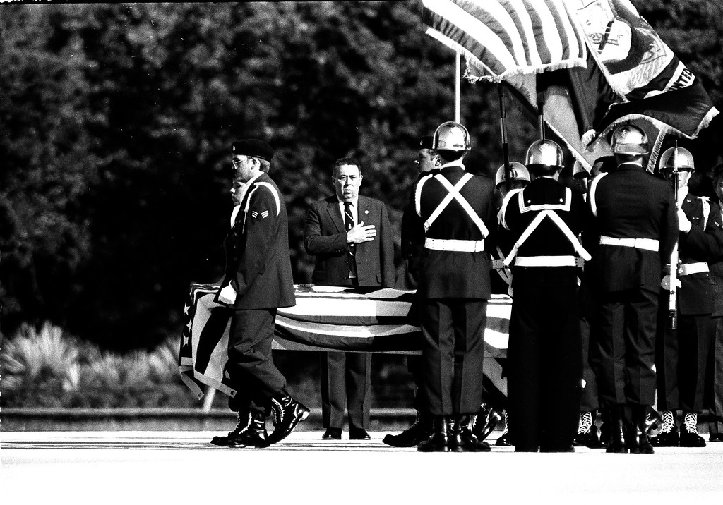 . The bodies of the seven space shuttle Challenger astronauts, killed in an explosion after take off Jan. 28, are carried by an honor guard past Chief of Flight Crew Operations, George Abbey as they are loaded aboard a C-141B Starlifter, April 29, 1986.  (AP Photo/Paul Kizzle)
